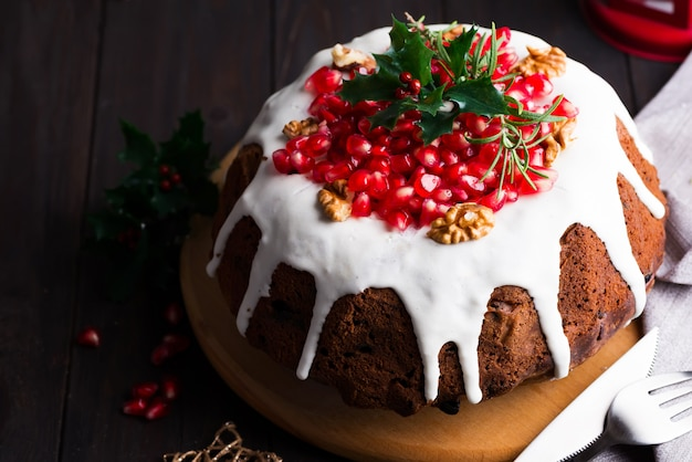 Christmas chocolate cake with white icing and pomegranate kernels on a wooden dark  with red lantern