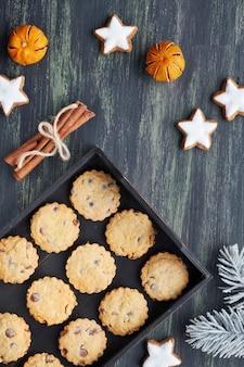 Рождественские шоколадные печенья, плоские лежал со специями и зимние украшения на темном.