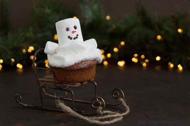 Christmas chocolate cupcakes with snowman decor. on dark background.