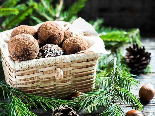 Christmas chocolate truffles in a wicker box the fir tree branches on wooden table