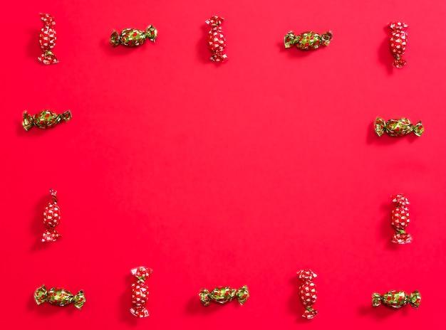 Рождественские шоколадные конфеты, образующие рамку на красном фоне, чередующиеся шоколадные конфеты с красной и зеленой оберткой