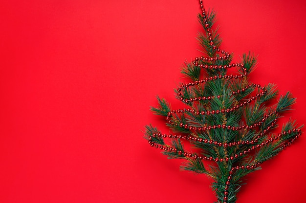 Christmas or christmas ornaments: branches of a christmas tree in the form of christmas tree with red beads on red with copyspace