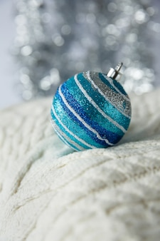 Christmas. christmas toy silver, blue striped ball with sparkles on a white knitted woolen sweater.