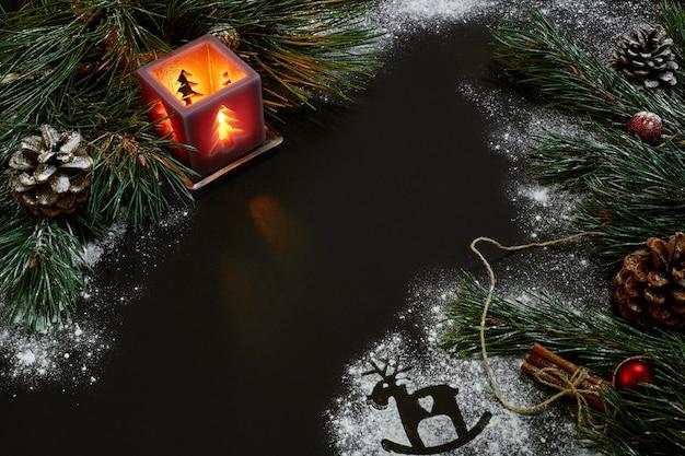 Рождество, рождественская елка, свеча, снег, шишки и палочки корицы на черном фоне. вид сверху. скопируйте пространство. натюрморт. заложить квартиру новый год