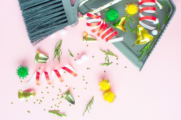 Рождественская уборка после. чистящие инструменты веник и совок и неиспользованные рождественские украшения после плоской планировки с видом сверху. концепция уборки после отпуска, убрать беспорядок.