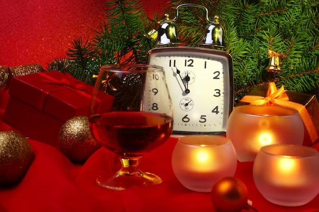 Рождественские часы, бокал с коньяком или виски и свечи. новогоднее украшение с подарками, елочными шарами и елкой. концепция празднования нового года.