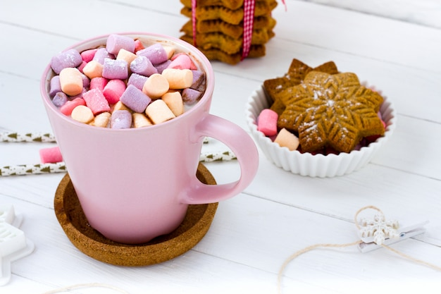 Christmas cocoa marshmallow pink cup and ginger biscuit white wooden table