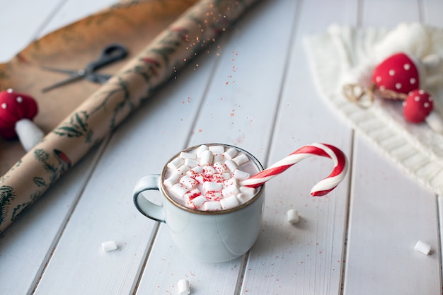Christmas cocoa with candy cane, marshmellow and falling red sugar on white wooden table surrounded by new year entourage.