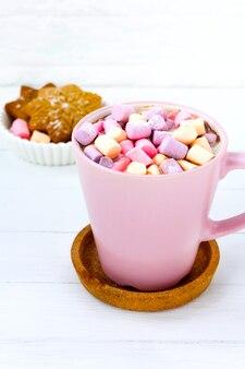 ピンクのカップにマシュマロと木製のテーブルに生姜のビスケットとクリスマスココア
