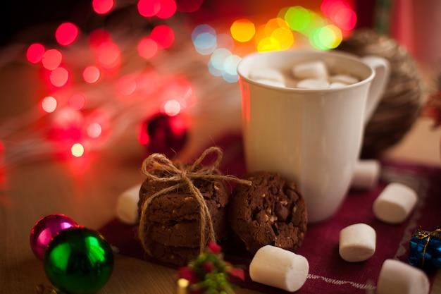 마시멜로를 곁들인 크리스마스 코코아와 초콜릿과 견과류를 곁들인 수제 쿠키 새해 뜨거운 음료