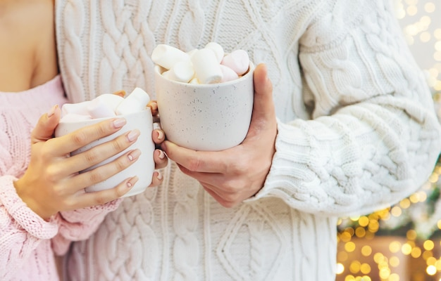 Christmas cocoa with marshmallows in the hands of a man and a woman, selective focus.