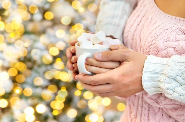 남자와 여자의 손에 마시멜로와 함께 크리스마스 코코아. 휴일. 선택적 초점입니다.