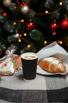 Рождественский кофе и круассаны с подарками и игрушками на фоне елки