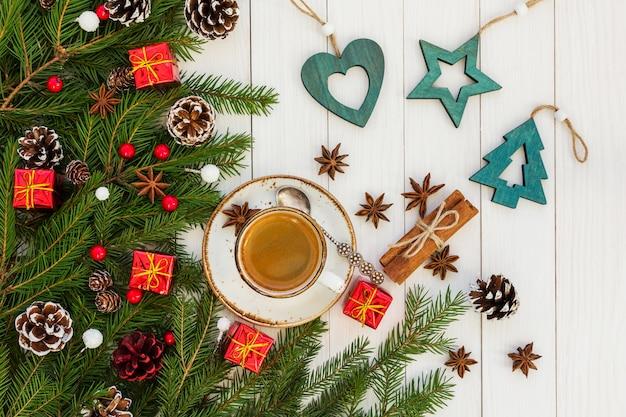 クリスマスコーヒー。青いクリスマス装飾が施された白い木製テーブルの上のコーヒーカップ。上面図