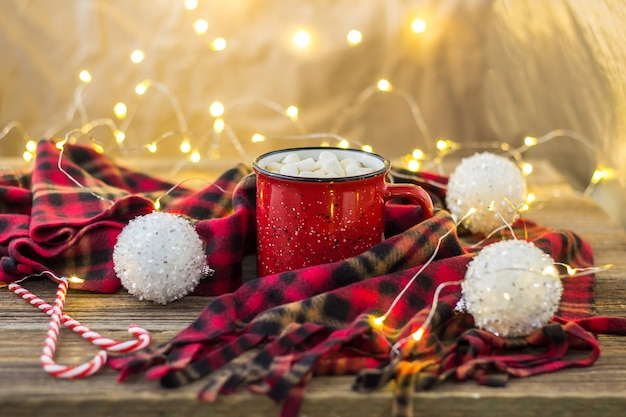 Рождественский кофе в красной чашке с зефиром и клетчатым пледом. украшенные белыми шарами конфета и светлая гирлянда боке
