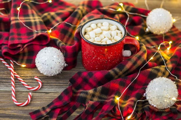 Рождественский кофе в красной чашке с зефиром и клетчатым пледом. новогодняя концепция украшена белыми шарами конфетой и легкой гирляндой боке