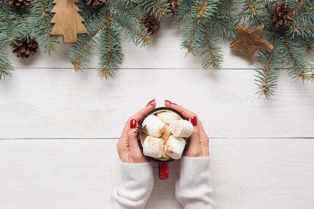 手でクリスマスコーヒーと常緑樹のモミの木の装飾的なお祝いフレーム