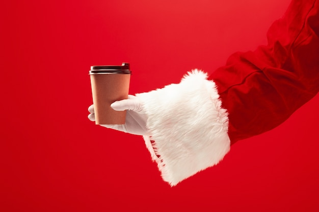 Christmas coffee. the santa hand holding cup of coffee isolated on a red