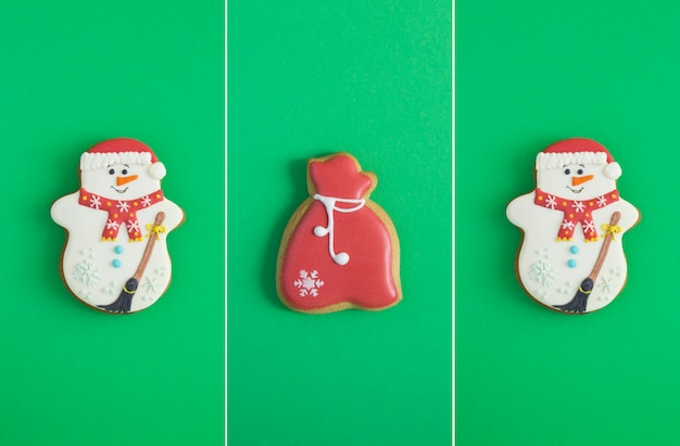 Christmas collage. christmas gingerbread in the shape of a snowman and gift on the green background. copy space.
