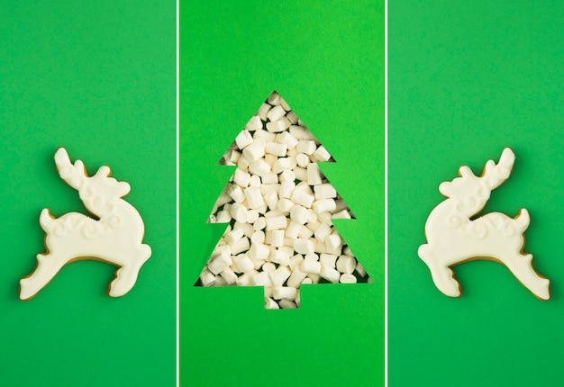 Christmas collage. christmas tree cut out on the green background and gingerbread in the form of white deer.
