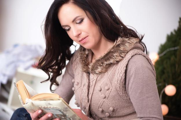 クリスマス、快適さ、レジャー、人々のコンセプト-本を読んで幸せな若い女性のクローズアップ