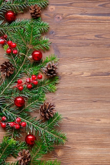 Christmas compisition with xmas tree and red berries on wooden table