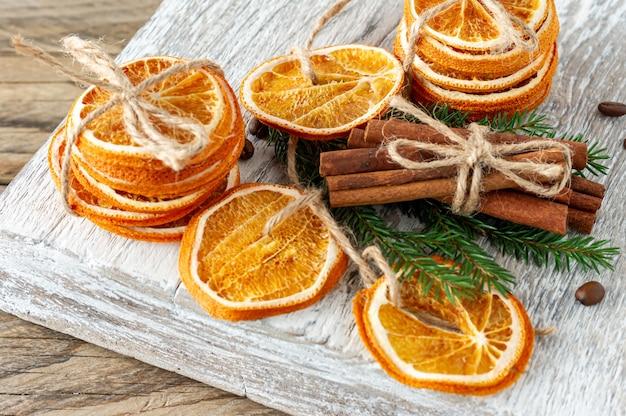 Новогодняя композиция. композиция из сухих апельсинов, палочек корицы, ветвей дерева меха и грецких орехов на деревянном фоне. деревенские, праздничные ингредиенты специй.
