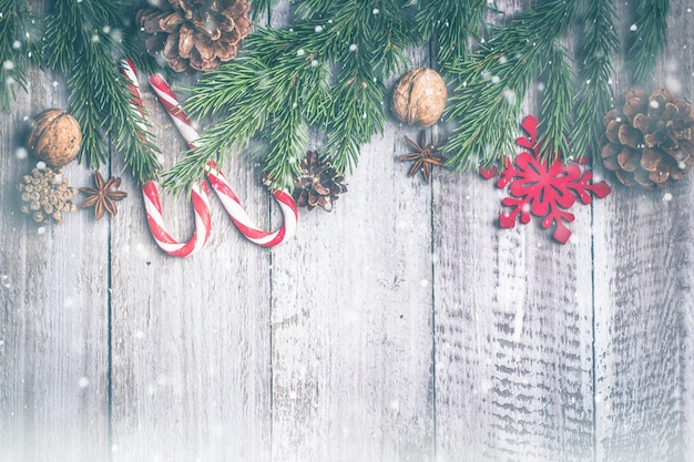 Christmas composition background. sweet candy sticks, pine cones, fir branches on wooden b