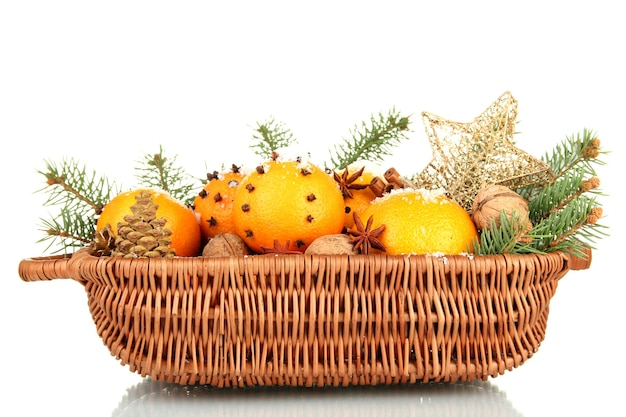 Christmas composition in basket with oranges and fir tree, isolated on white