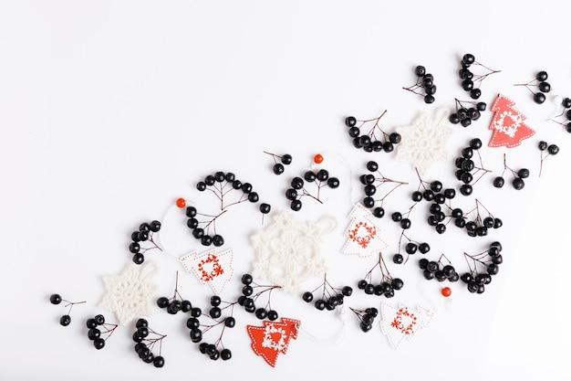 Новогодняя композиция. черные ягоды аронии, белые вязаные снежинки и бело-красные елки на белом фоне. новый год, зимняя концепция. плоская планировка, вид сверху, копия пространства