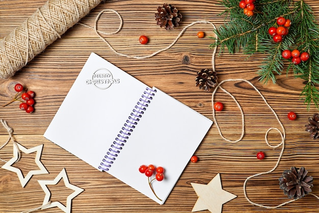 Christmas composition of blank notepad with the inscription merry christmas on wooden background
