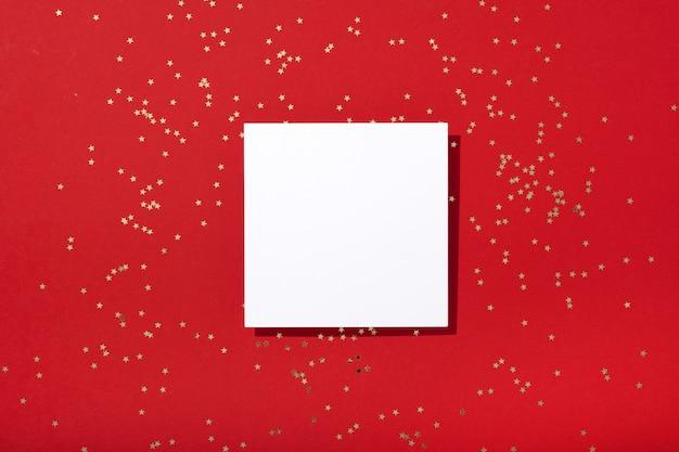 Новогодняя композиция. чистый квадратный бумажный макет, украшения с золотыми звездами и конфетти на красном фоне