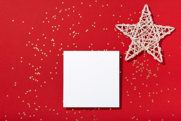 크리스마스 구성입니다. 빈 사각형 종이 모형, 빨간색 배경에 황금 별 색종이 보석