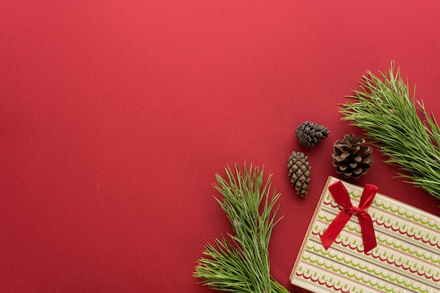 Christmas composition. a box with a gift and spruce branches on a red background. spruce cones and christmas decorations. flat lay, top view, space for text