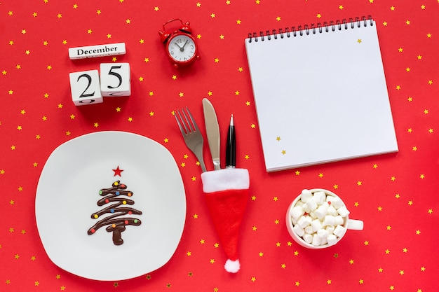 Christmas composition calendar december 25th sweet chocolate christmas tree on plate, cutlery in santa hat cup of cocoa