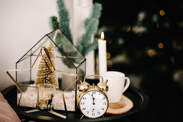 クリスマス作曲。キャンドル、カップコーヒー、ヴィンテージゴールドの時計、テーブルの上の星の形をしたメタルゴールドのキャンドルホルダー。自宅のインテリアと装飾。閉じる。クリスマス休暇の前夜。