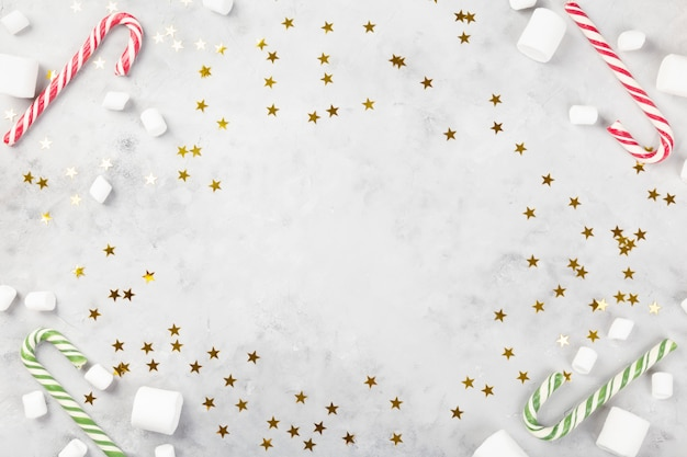 Новогодняя композиция. карамельный тростник на сером бетонном фоне с сверкающими звездами. концепция зимних праздников, нового года, рождества. вид сверху. копировать пространство