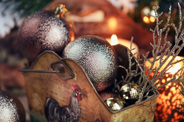 クリスマス作曲。モミの木の枝、キャンドル、休日が木製の背景に光るクリスマスと新年の装飾