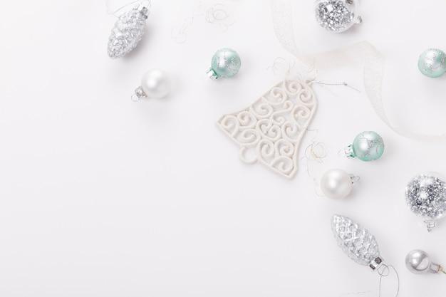 クリスマス作文。クリスマスボール、白地に青と銀の装飾。フラットレイ、上面図、コピースペース