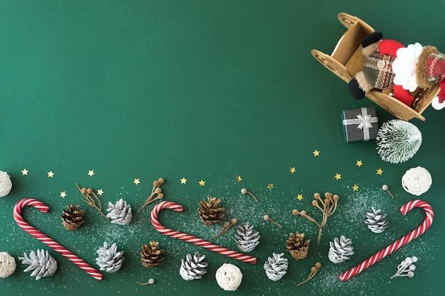 クリスマス作文。クリスマスのお菓子、ギフト、装飾、松ぼっくり、緑の背景におもちゃ。フラットレイ、上面図、コピースペース
