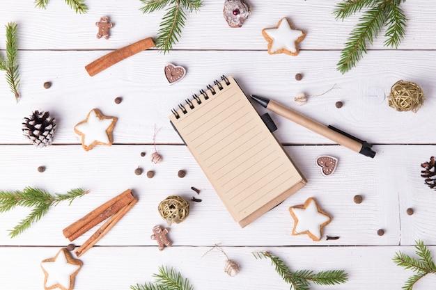 크리스마스 구성입니다. 향신료 정향, 씨앗, 견과류, 메모장, 펜, 나무 흰색 배경에 소나무 콘 크리스마스 컵 케이크. 평평한 평지, 평면도.
