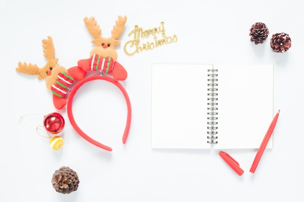 Christmas composition. christmas decoration, pine cones, notebook and red pen with copy space. flat lay, top view