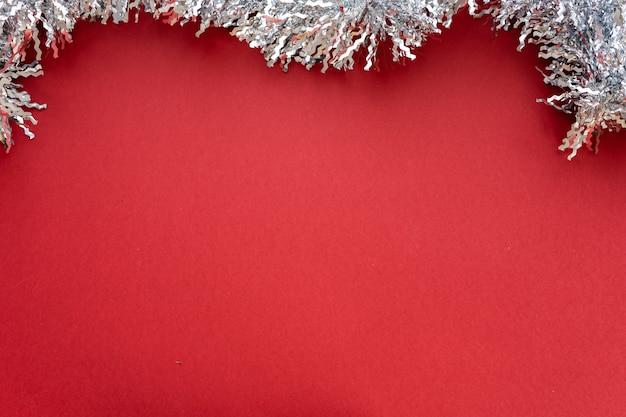 Новогодняя композиция. новогоднее украшение белая мишура на красном фоне. плоская планировка, вид сверху, место для текста