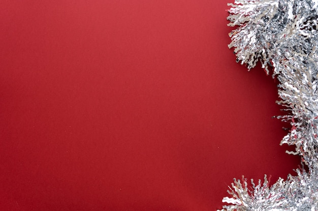 Christmas composition. christmas decoration white tinsel on a red background. flat lay, top view, space for text