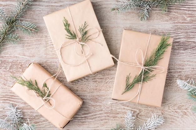 クリスマスの作曲。クリスマスのモミの木の枝、ギフト、木製の白い素朴な背景に松ぼっくり。フラットレイ、上面図。スペースをコピーします。バナーの背景