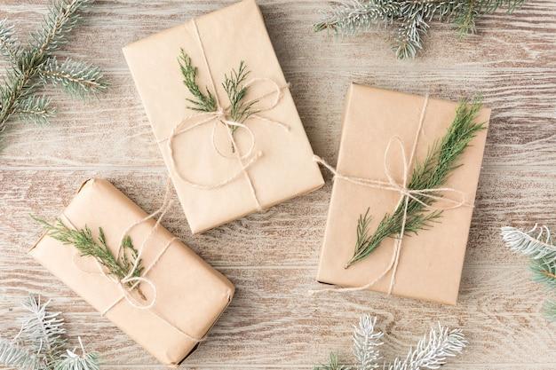 クリスマス作文。クリスマスのモミの木の枝、ギフト、木製の白い素朴な背景に松ぼっくり。フラットレイ、上面図。スペースをコピーします。バナーの背景