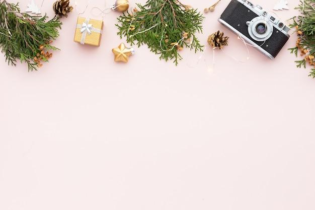 크리스마스 구성입니다. 분홍색 배경에 선물, 황금 소나무 콘, 녹색 나뭇가지, 장식이 있는 크리스마스 프레임. 평면도, 평면도, 복사 공간