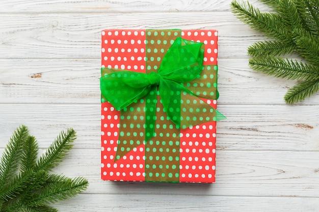 クリスマス作文。クリスマスプレゼントと木製の背景にモミの枝。フラットレイ、上面図、コピースペース