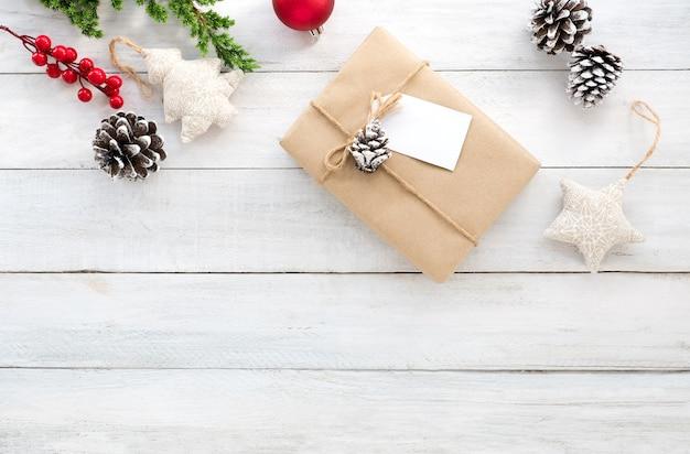クリスマスの組成。クリスマスのギフトボックス、松のコーン、モミの葉、ホリーベリーと白木製の背景に装飾素朴な要素。クリエイティブフラットレイ、トップビューデザイン