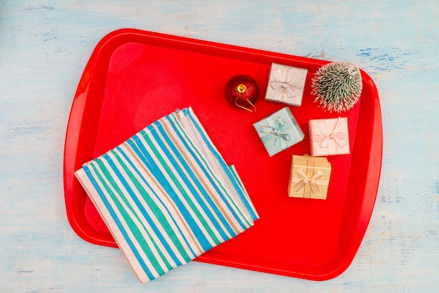 Christmas composition. christmas gift boxes. red plastic dining tray on the table.